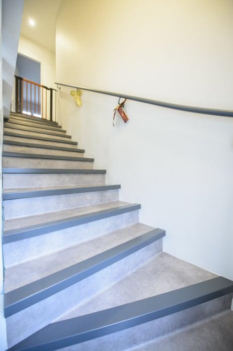 escalier à quart tournant moderne avec main courante en acier et marche habillage béton