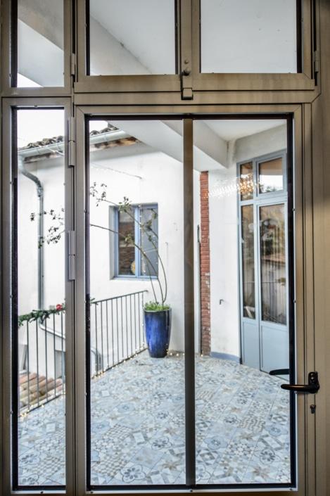 verrière avec porte d'entrée maison en métal