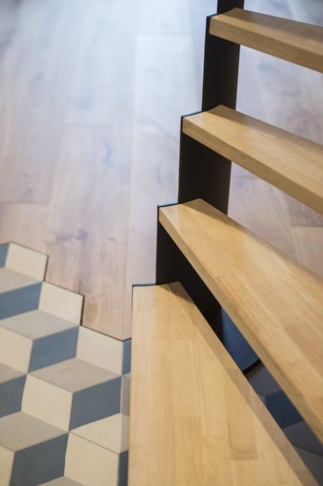 escalier design avec marche en bois clair et limon latéral en acier peint