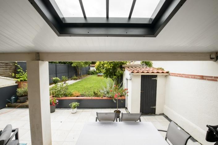 jardin avec terrasse en pierre et toit avec puit de lumiere moderne en metal