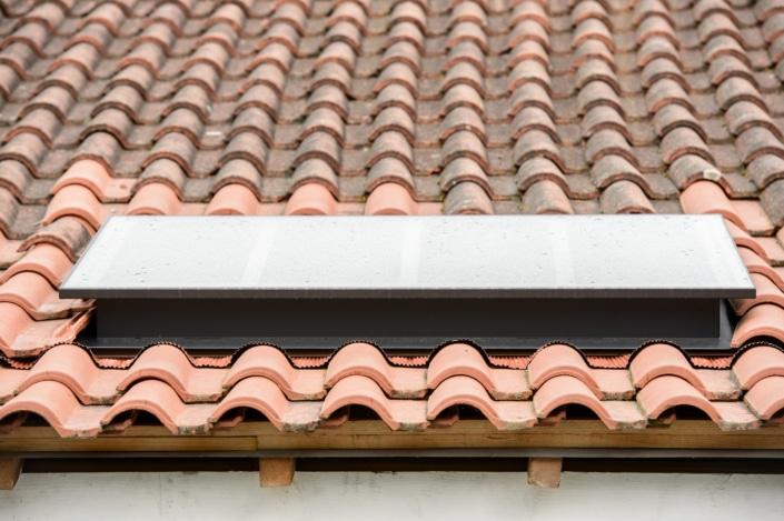 toit en tuiles rouges avec verriere exterieur en metal