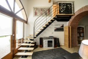 salon avec escalier quart tournant en bois et limon central en metal