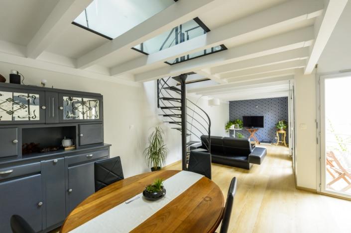 salon moderne avec escalier en fer et puit de lumière